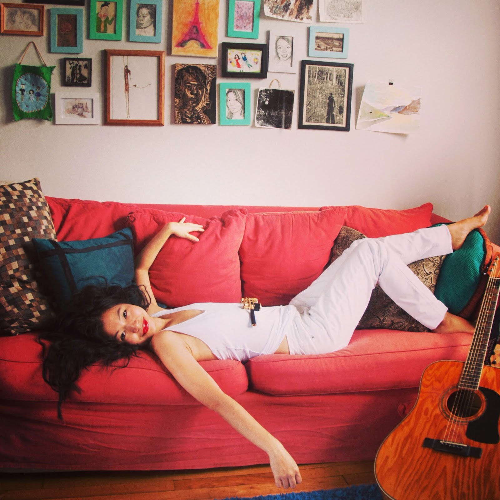red lips white pants white tank red couch guitar opera glasses cushions artwork