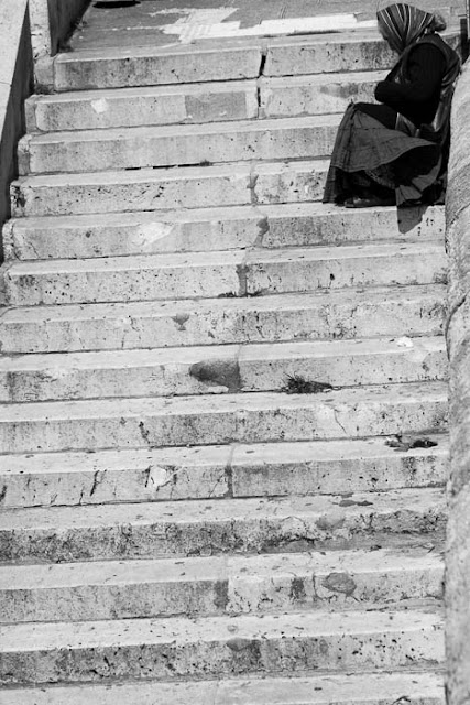 woman begging on stone steps in Paris