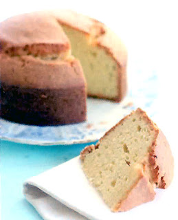 Classic madeira sponge cake with a wedge sliced out of the cake.