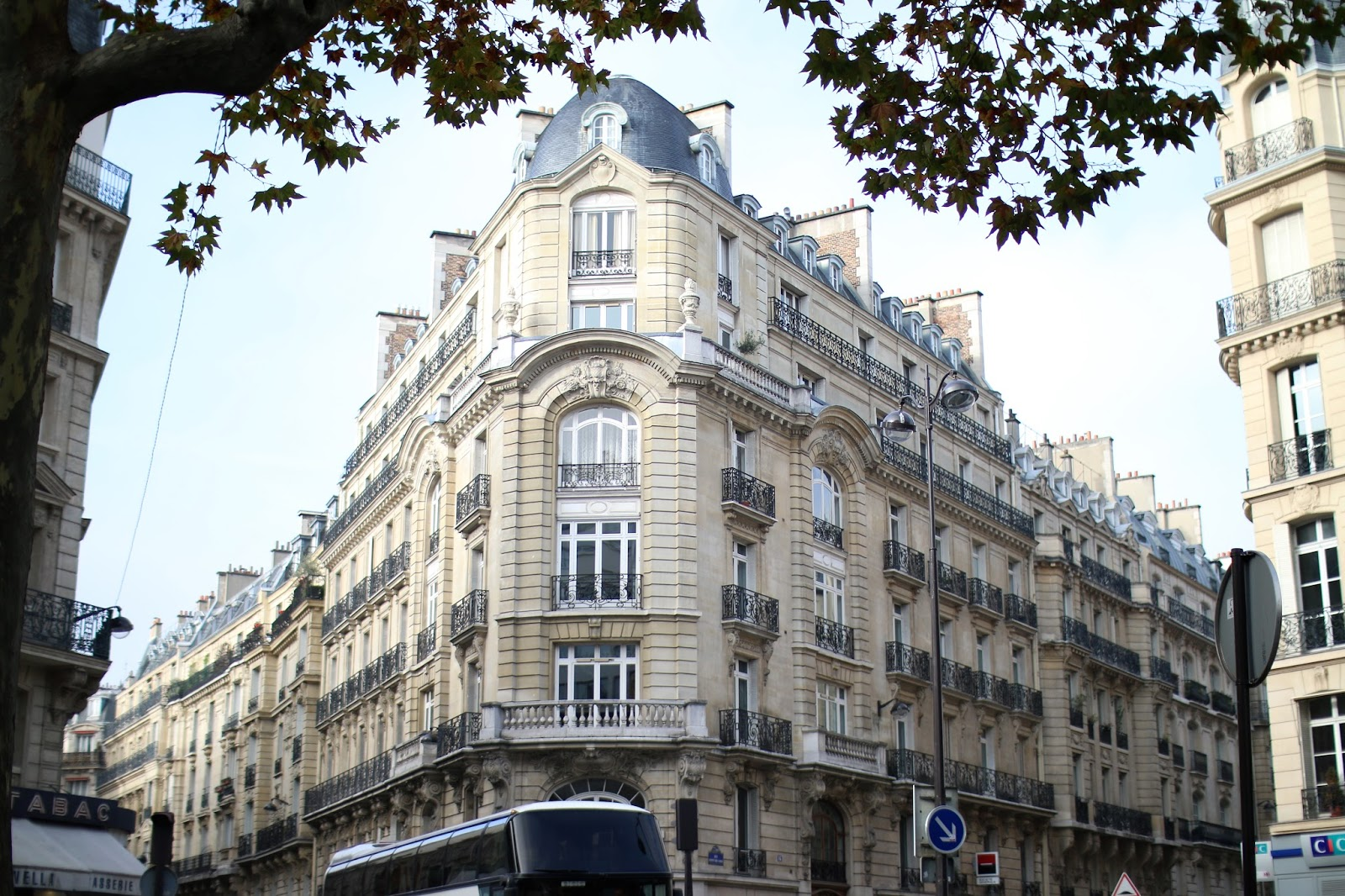 a beautiful neutral coloured building in paris with trees in the foreground