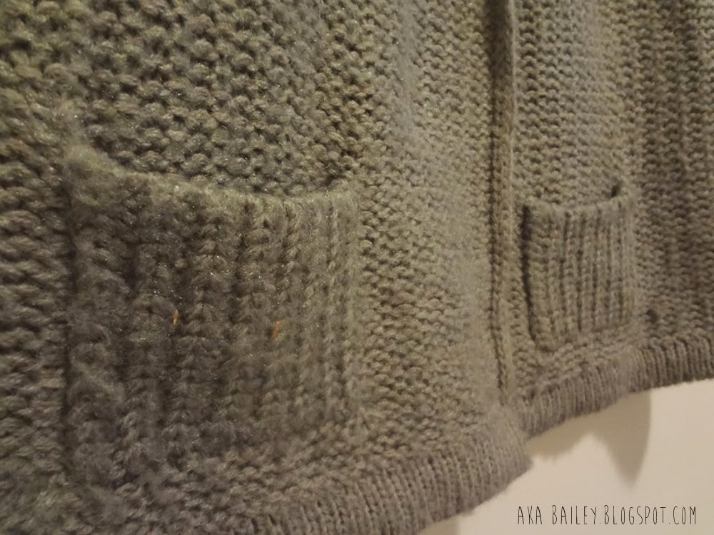 Front pockets on a taupe sweater