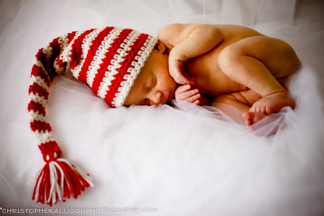 A newborn baby sleeping in a red and white hat