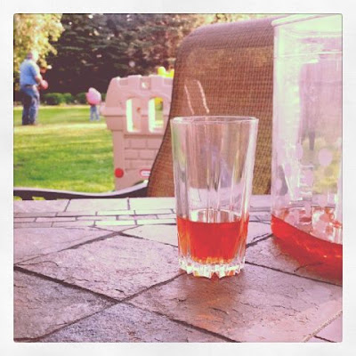 Glass of tea in the backyard with Kirsten and Daddy playing in the background