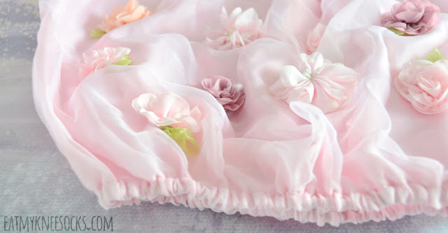 Close-up of the elastic hemline, organza overlay, and floral applique on Romwe's pastel pink boat neck off-shoulder dress.