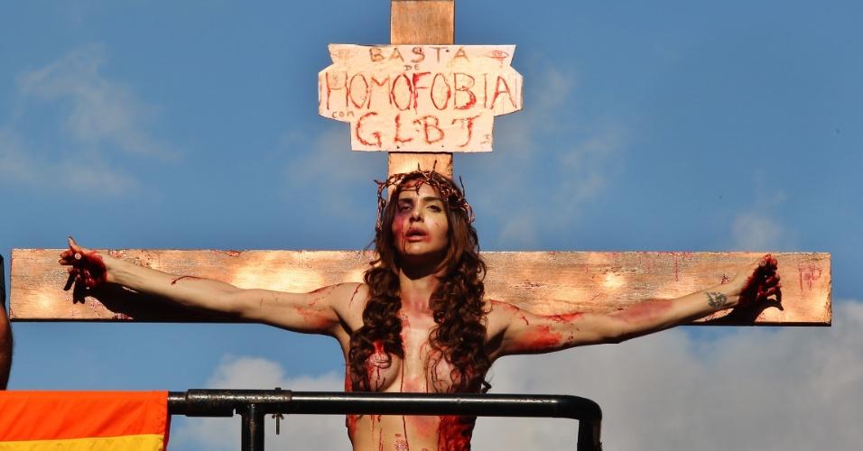 """A atriz Viviany Beleboni, de 26 anos, durante a 19ª Parada do Orgulho LGBT de São Paulo. Ela se prendeu à cruz, encenando o sofrimento de Jesus, para """"representar a agressão e a dor que a comunidade LGBT tem passado""""."""