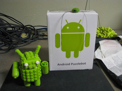 The awesome Lego Android mascot posing for the camera with a silly spider watching.