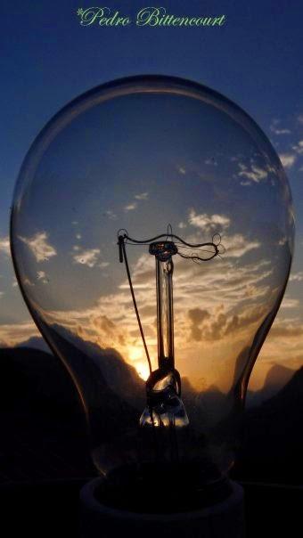 Descrição: Fotografia colorida, em primeiro plano uma lâmpada incandescente apagada. No centro da foto, os componentes, haste e filamento, dentro do bulbo transparente. Através do contorno do vidro, ao fundo, o por-do-sol dourado ladeia as montanhas escuras. Nuvens esparsas compõem o céu azul acinzentado . No topo em caligrafia verde lê-se: Pedro Bittencourt.  Fim da descrição.