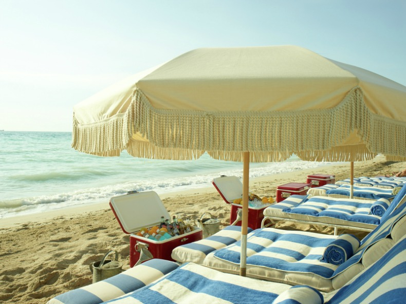 Coastal striped beach loungers with umbrellas