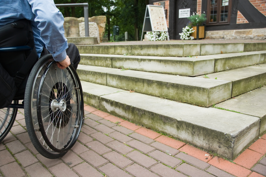 Man in a wheelchair facing a short set of stairs