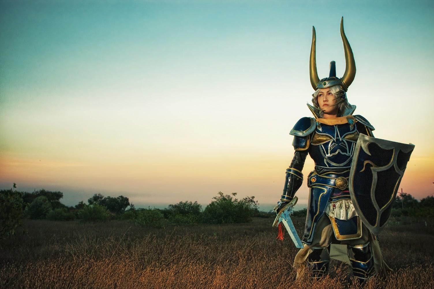 photo de cosplay féminin en armure, épée et bouclier  avec casque à cornes dans un champ