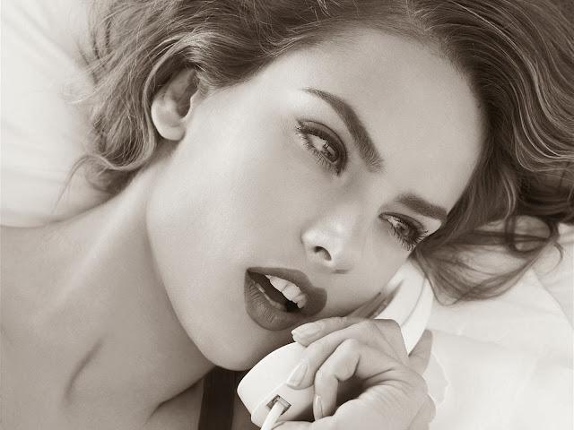 девушка с ярко накрашенными губами и лицом говорит по телефону в постели