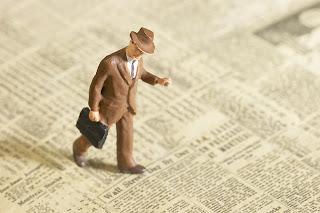 Man walks across newspaper