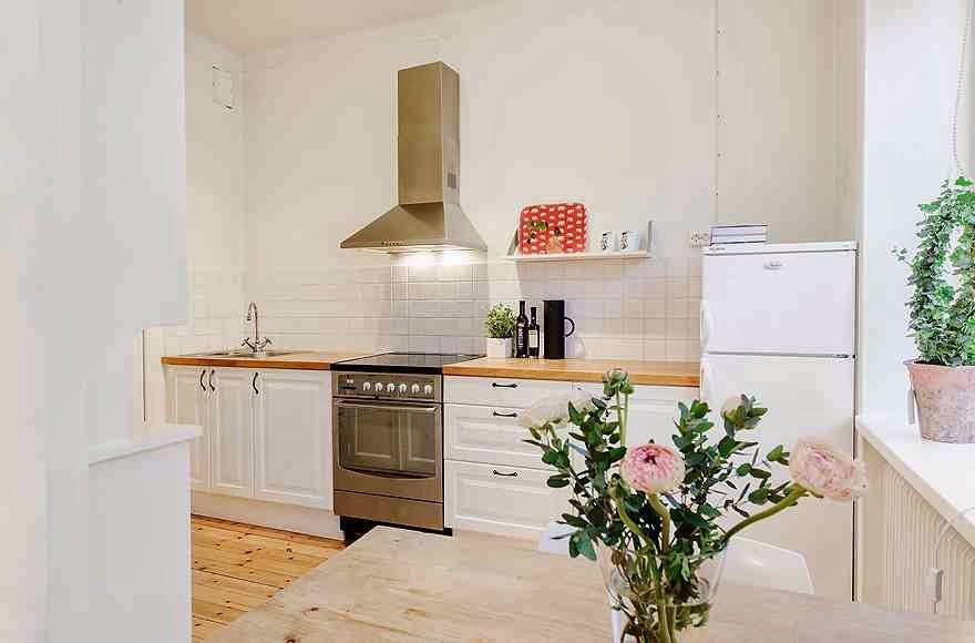 Długa kuchnia urządzona w skandynawskim stylu, białe meble kuchenne z czarnymi uchwytami