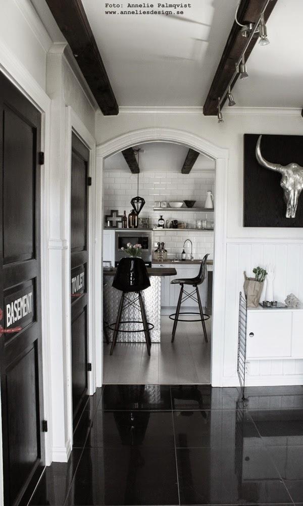 kök, svart och vitt, svartvit, svartvita, svarta dörrar, svartmålad dörr, text på dörr, industriellt kök, industrikök, industristil, plåt, rostfritt, rostfria hyllor, vitt kakel, köksö, hth köksskåp, kors, taklampa, string hylla, vitt, vit, vtita, svarta stora klinkersplattor i hallen, vitt plankgolv, öppna hyllor,