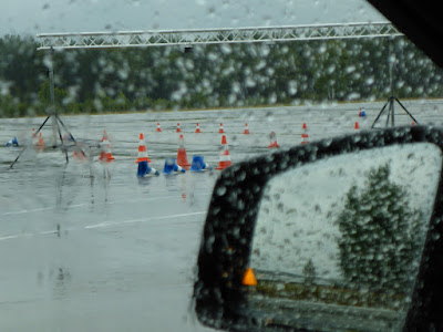 Blick durch eine regennasse Autoscheibe auf einen Fahrübungsparcours