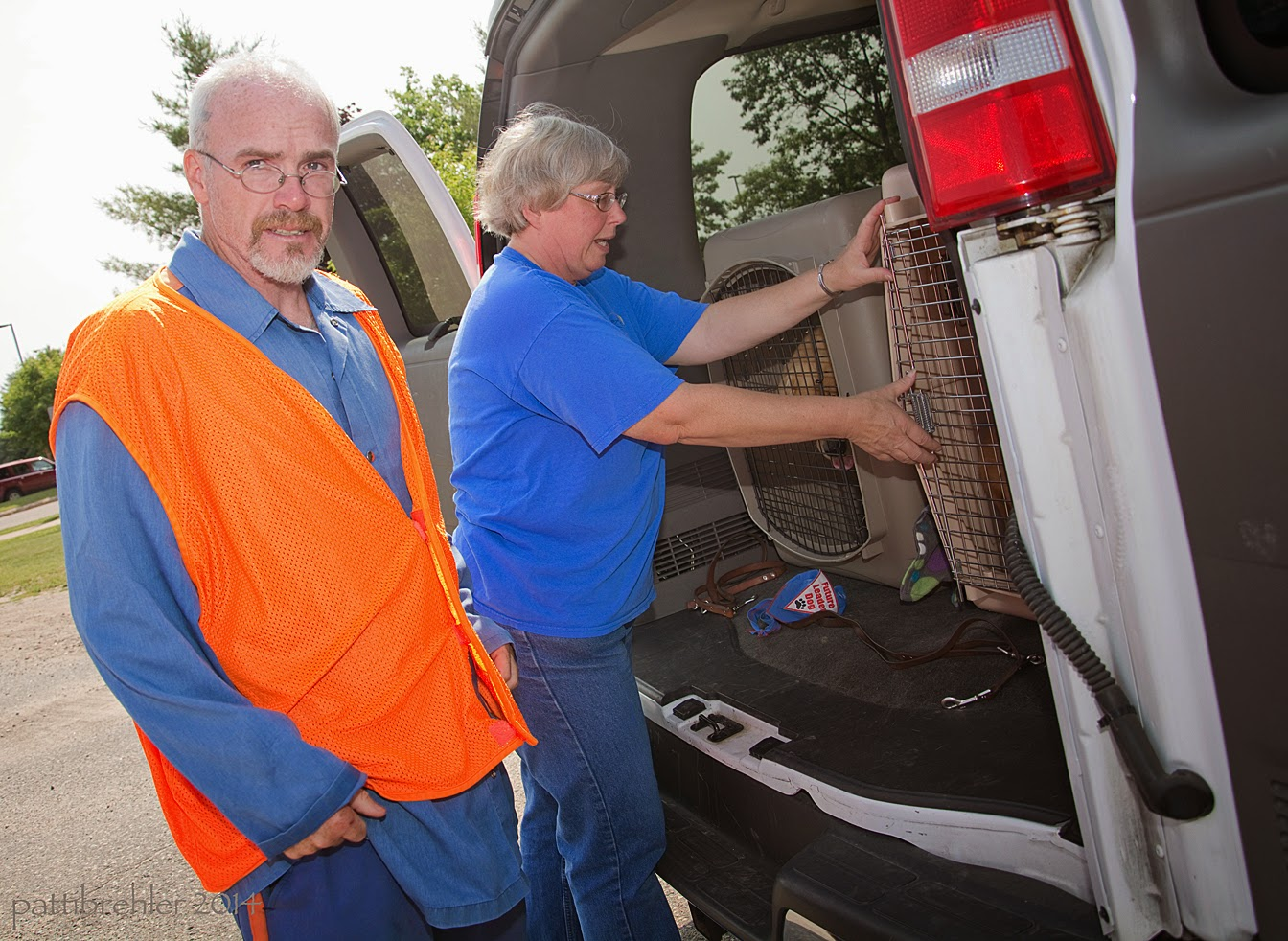 The man in the blue shirt and orange vest is turning away from the van and looking at the camera with a sad face. A woman wearing blue jeans and a blue t-shirt is closing the door of the airline crate.
