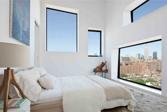 small guest bedroom with shag rug and a view of the NYC at the foot of the bed