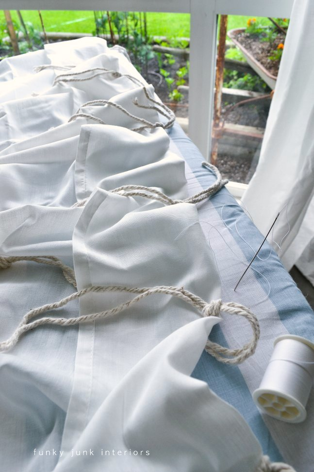 Making sheet curtains with mop string tab ties, and pipe curtain rods via Funky Junk Interiors