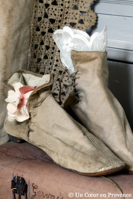 Old pair of boots decorated with a piece of lace and a flower fabric