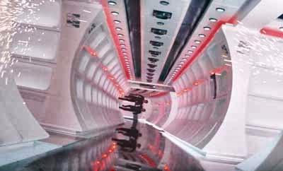 Plano interior del Enterprise que muestra un pasillo, con un cruce en primer plano. Kirk y Scotty están corriendo por una de las paredes del pasillo, como si fuera el suelo.