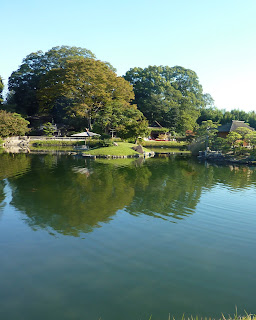 Big pond with little islands and with the water reflecting trees in Korakuen Garden, Okayama
