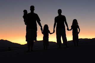 silhouettes of family holding hands