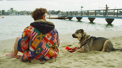 Man in colorful flag jacket with his dog sitting on the beach