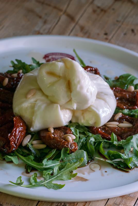 ensalada de burrata con tomates secos, rúcula y piñones