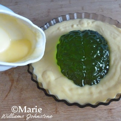 Glass dish with green lime jello middle and thick custard poured around it