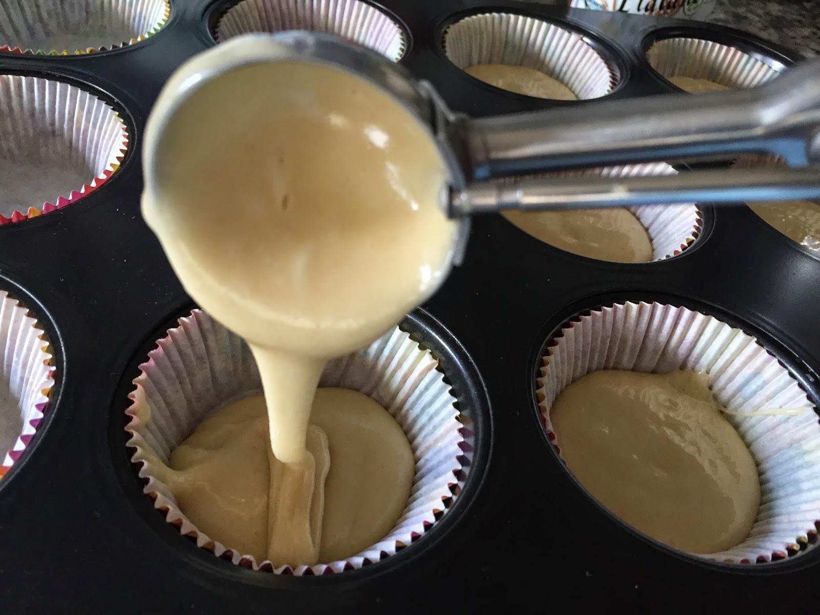 Magdalenas rellenas de mermelada, rellenando moldes con la masa.