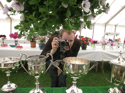 Photographer peering out from under a hanging basket