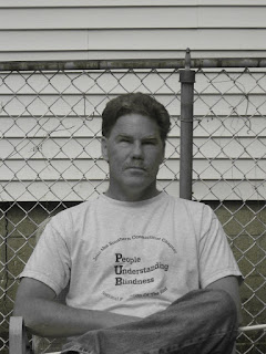 Black and white photograph of a serious-faced man with short wavy hair and a mustache. He's sitting outside in jeans and a white T-shirt that says People Understanding Blindness.