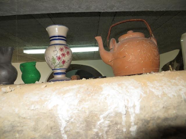 Peças de cerâmica de barro em cima de viga de pedra de cantaria