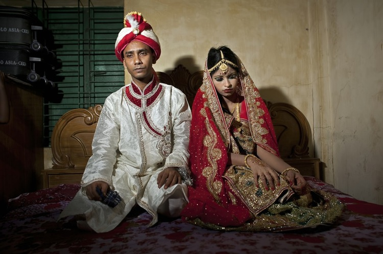 70 Of The Most Touching Photos Taken In 2015 - Mohammad Hasamur Rahman, 32, sits with this new bride, 15-year-old Nasoin Akhter, in Manikganj, Bangladesh. Photographer Allison Joyce described her as the