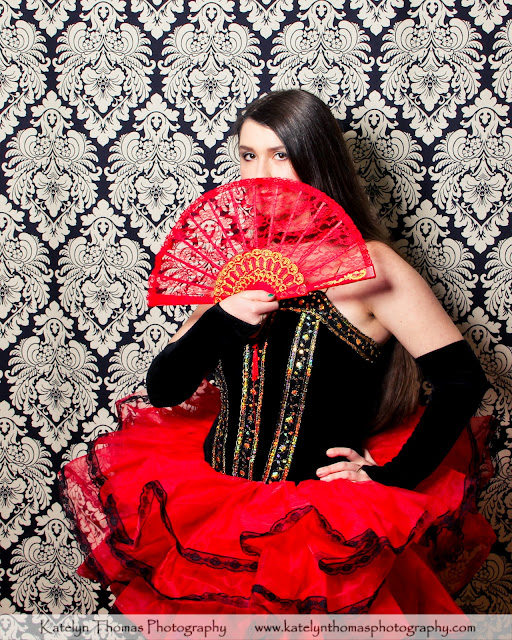Dancer with a red fan wearing a flamenco costume