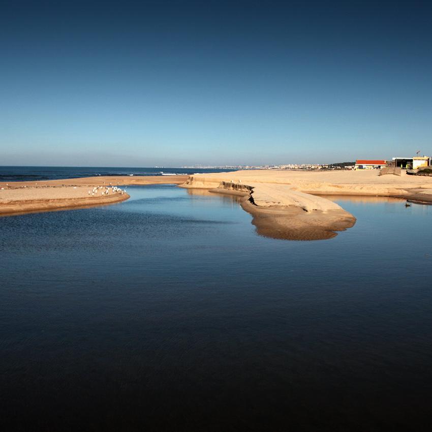 Foto com o lago em primeiro plano, a seguir uma língua de areia e por fim o mar e o céu limpo