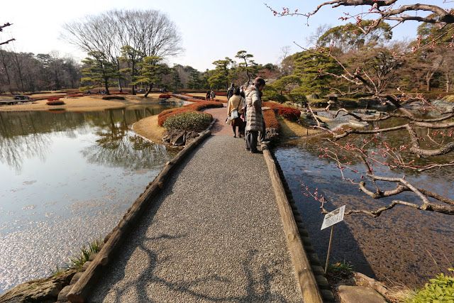 Crossing a little bridge over the pond in the beginning of Spring at Imperial Palace East Garden in Tokyo, Japan