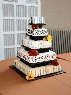 5 tier white wedding cake with black scrolls and red roses