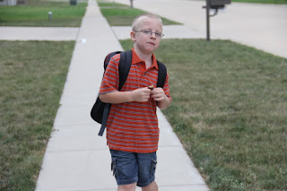 boy with backpack walking on sidewalk