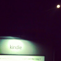 reading on an Amazon Kindle Touch in the moonlight