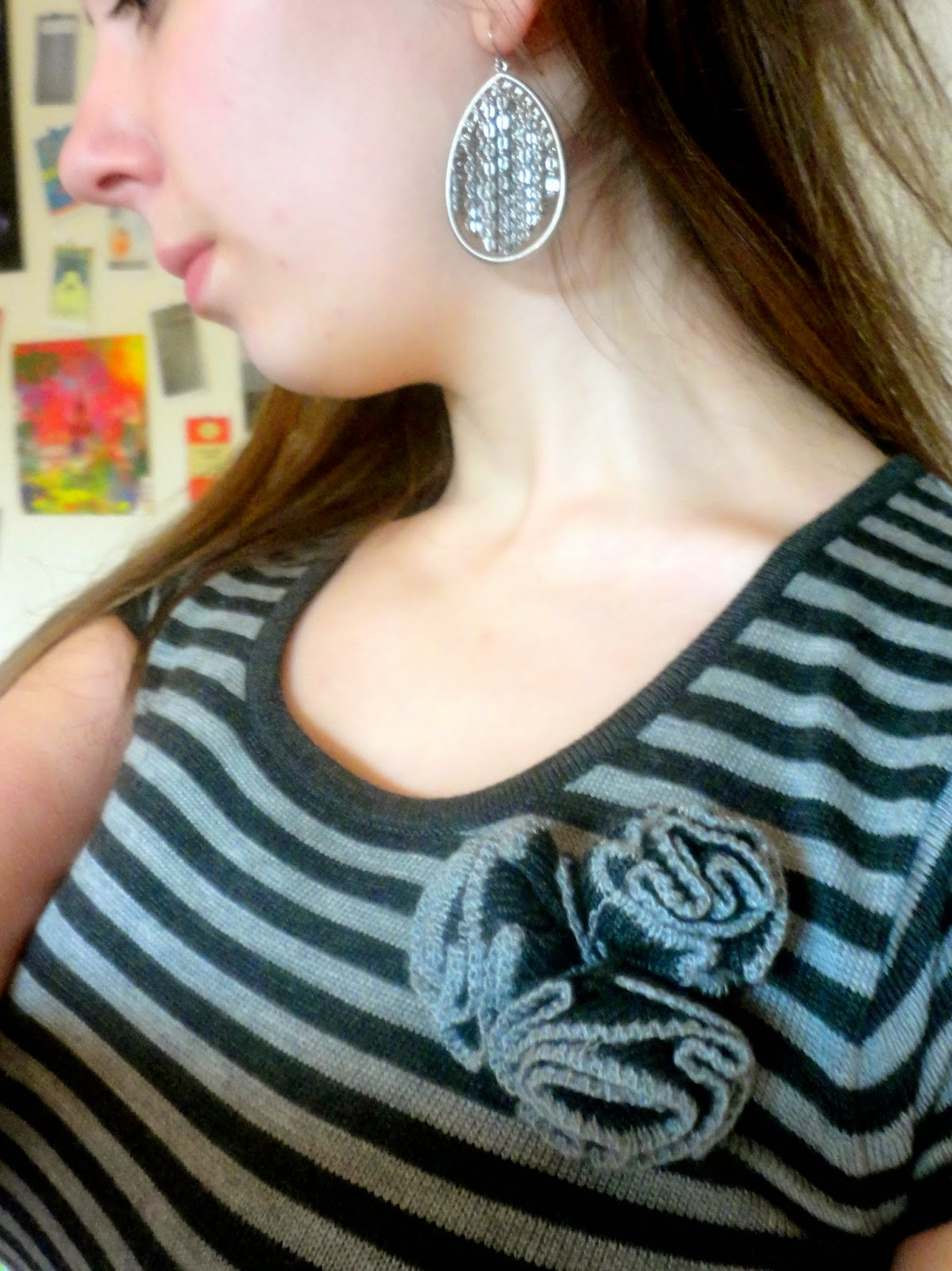 Outfit jewellery details, of black and silver chain & hoop earrings, and knitted flower on grey dress