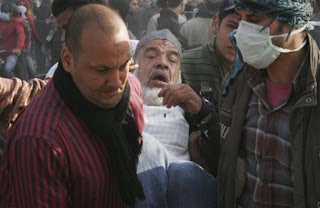 Egyptian men carry an injured elderly protester during clashes with Egyptian riot police