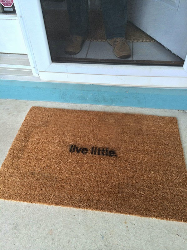 "a door mat with ""live little"" spray painted on it."