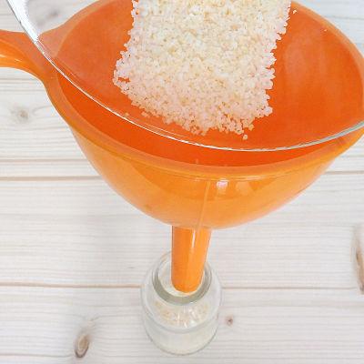 Una mano echando sal con un embudo en un frasco de cristal