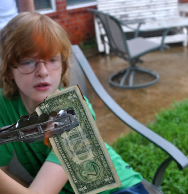 child burning a one dollar bill
