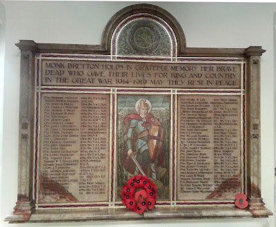 "A large alabaster tablet.  The top section has the inscription ""Monk Bretton holds in Grateful Memory her Brave Dead who gave their lives for King and Country in the Great War 1914-1919 May they Rest in Peace"" surmounted by a semi circular extension enclosing a wreath.  Below are three panels, the central one holds a picture of St George, on either side are the lists of names.  The whole is surrounded by a mosaic border and carved raised borders in the stone.  There is a ledge below on which is resting a poppy wreath."
