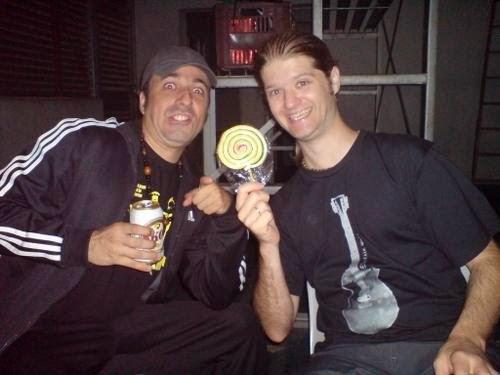 Fábio Corniani segurando uma lata de cerveja e fazendo careta e Marco Bonito segurando um pirulito