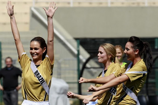 Miss Brazil 2011 Priscila Machado celebrates with team-mates Miss Australia 2011 Scherri-Lee Biggs and Miss Canada 2011 Chelsae Durocher after scoring a goal