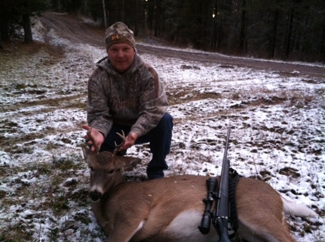 Idaho whitetail buck with rifle