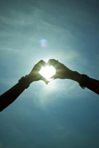 Dłonie ułożone w kształt serca na tle słońca.
